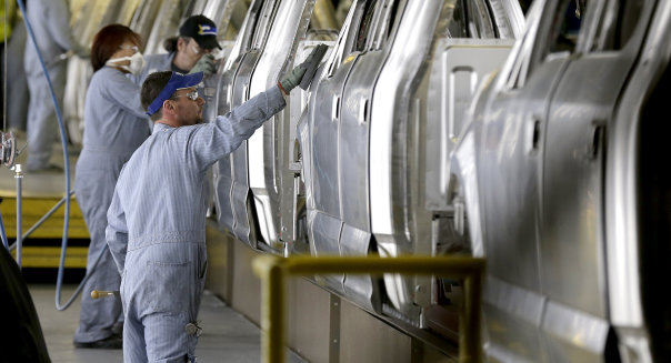 FILE - In this March 13, 2015 file photo, workers inspect the new aluminum-alloy body Ford F-150 trucks before they get painted at the company