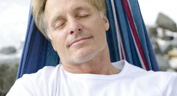 blonde mature man sleeping in hammock